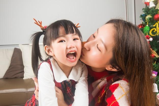 행복 한 엄마와 집에서 크리스마스 트리와 선물을 장식하는 작은 딸