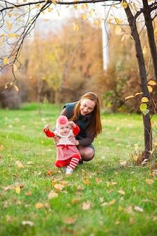 Счастливая мать и дочка играют в осеннем парке
