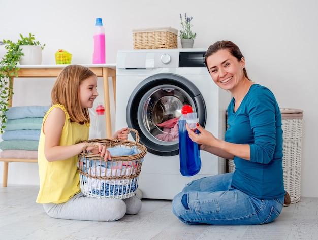 Счастливая мать и маленькая дочь стирают одежду с помощью машины в светлой комнате