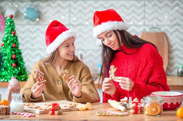 幸せな母と小さな女の子がキッチンでクリスマスクッキーを調理します