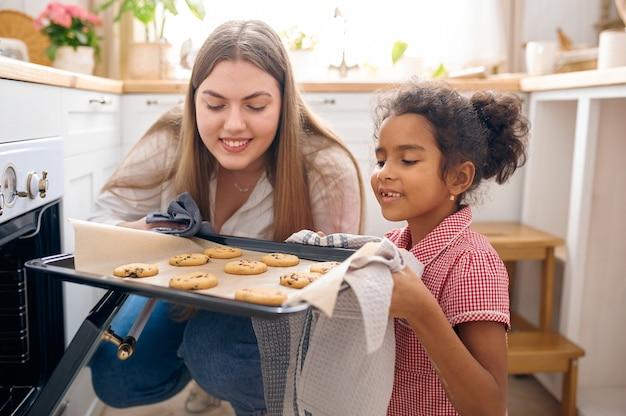 행복한 엄마와 어린 아이가 아침에 오븐에서 케이크를 요리합니다. 아침에 부엌에서 웃는 가족. 엄마는 여자 아이를 먹여, 좋은 관계
