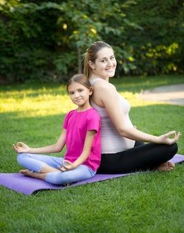 Счастливая мать и улыбающаяся дочь практикуют йогу и сидят спиной к спине в парке