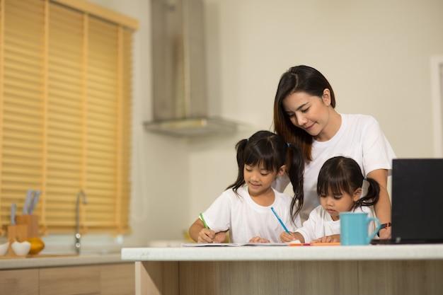 幸せな母と笑顔の娘が一緒にマーカーを使用して絵を描いています。養子縁組の子供をアートの宿題で手伝う母親。陽気な母親とアジアの少女が家で絵を描いています。