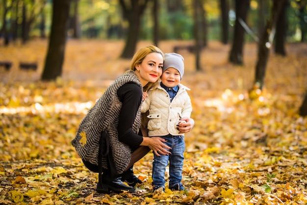 幸せな母と息子が秋の公園で遊んでいます。