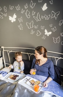 Счастливая мать и сын завтракают в постели у себя дома утром