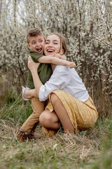 Счастливая мать и сын, весело вместе. мать нежно обнимает сына. на заднем плане цветут белые цветы. день матери