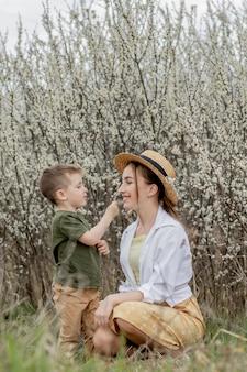 Счастливая мать и сын весело вместе. мать нежно обнимает сына. на заднем плане распускаются белые цветы. день матери.