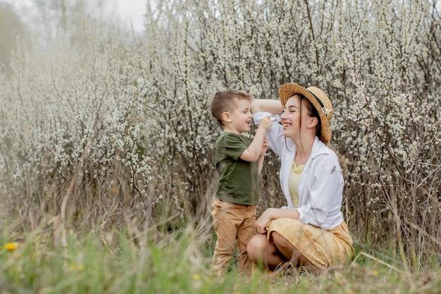 행복한 엄마와 아들이 함께 즐거운 시간을 보내고 있습니다. 어머니는 부드럽게 그녀의 아들을 안아줍니다. 배경에는 하얀 꽃이 핀다. 어머니의 날.