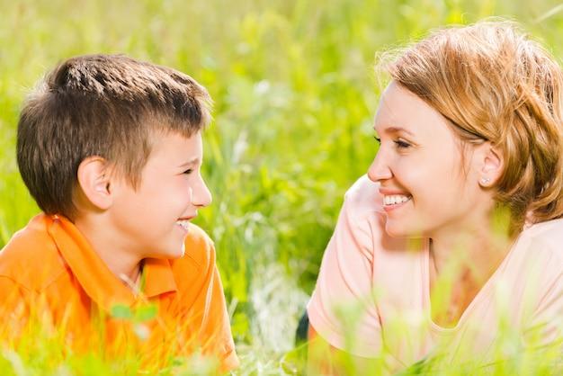 公園の屋外の肖像画で幸せな母と息子