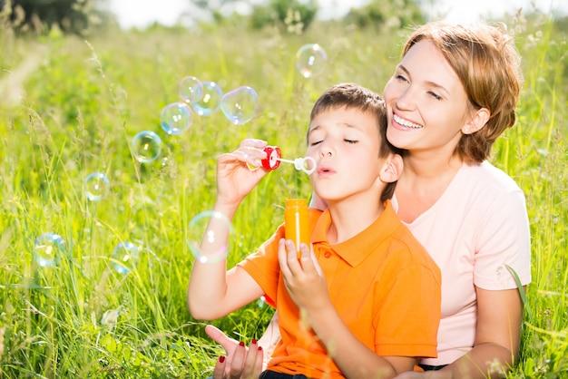 Счастливая мать и сын в парке, дует мыльные пузыри на открытом воздухе портрет