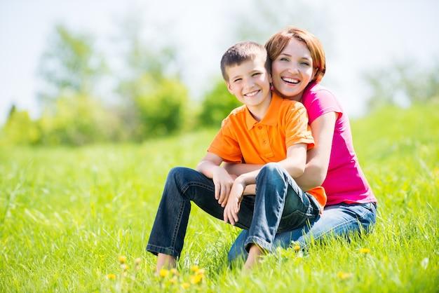春の牧草地の屋外の肖像画で幸せな母と息子
