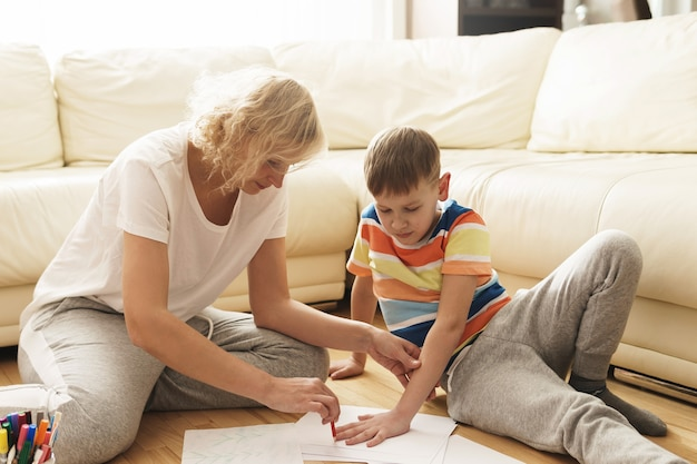 Счастливая мать и сын рисуют вместе дома