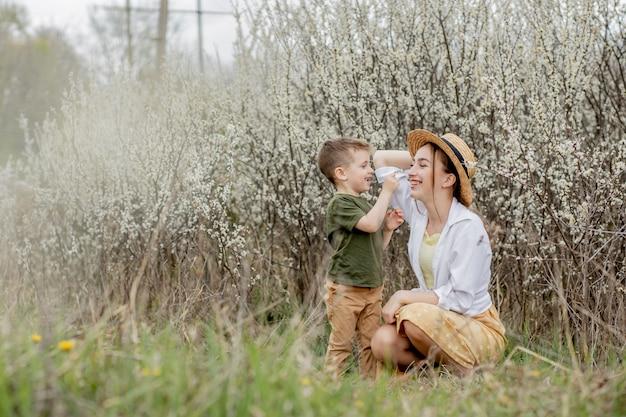 Счастливая мать и сын на поле с цветами