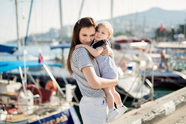 Счастливая мать и сын на фоне морской яхты