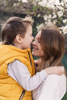 幸せな母と息子は花の咲く木と対戦します