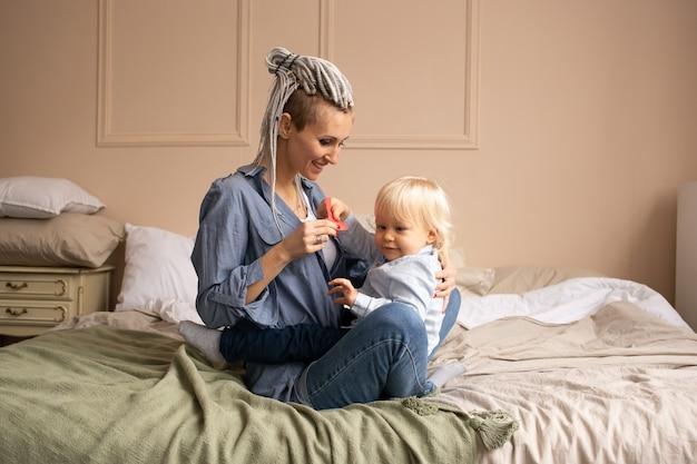 행복 한 엄마와 아들이 집에서 놀고 껴 안고. 침대에서 편안한 가족