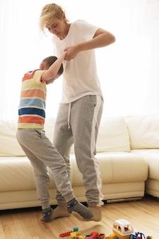 Счастливая мать и сын, играя дома в солнечный выходной день