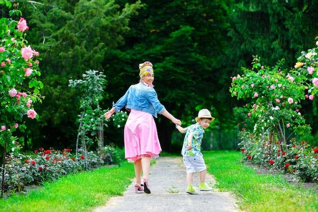 幸せな母と息子の花で夏の公園を歩きます。
