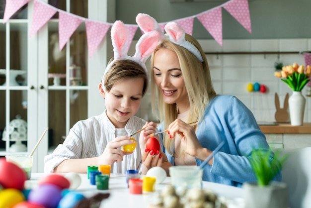 행복 한 어머니와 아들 부활절을 준비 하 고 계란 그림 토끼 귀 입고. 근접 촬영 초상화