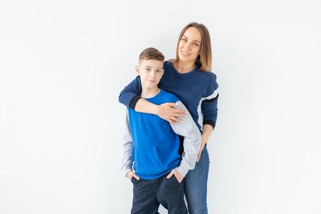 Счастливая мать и сын-подросток смеются и обнимаются на белой стене с копией пространства