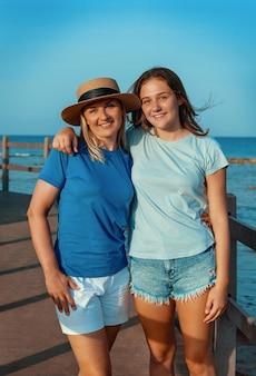 Счастливая мать и дочь-подросток, стоя на пирсе на берегу моря, обнимая и улыбаясь, макет футболок. любящая семья проводит время вместе на открытом воздухе летом, наслаждаясь закатом