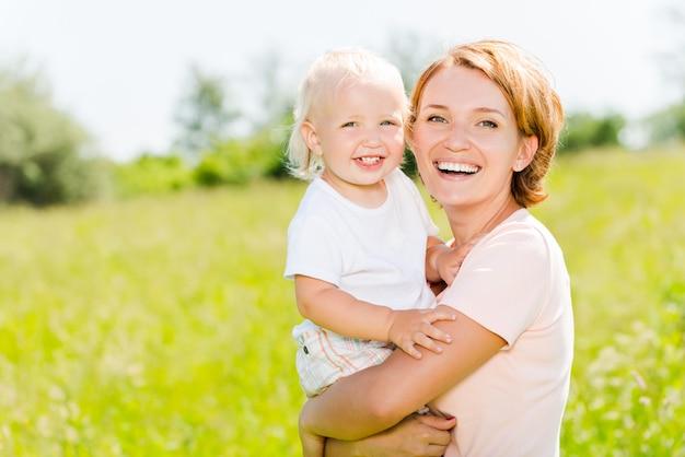 春の牧草地の屋外の肖像画で幸せな母と幼児の息子