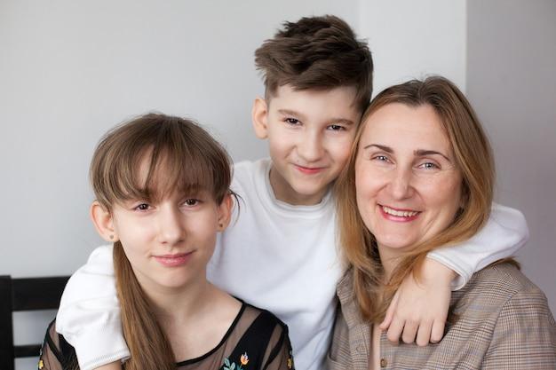Счастливая мать и двое детей дома. портрет улыбающейся мамы, обнимающей дочь и сына. концепция счастливой семьи