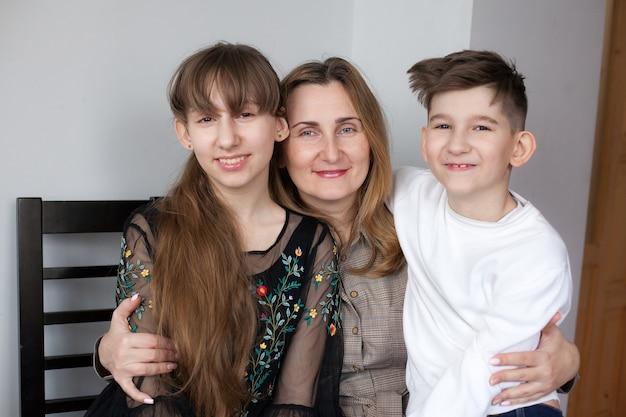 Счастливая мать и двое детей дома. портрет улыбающейся мамы, обнимающей дочь и сына