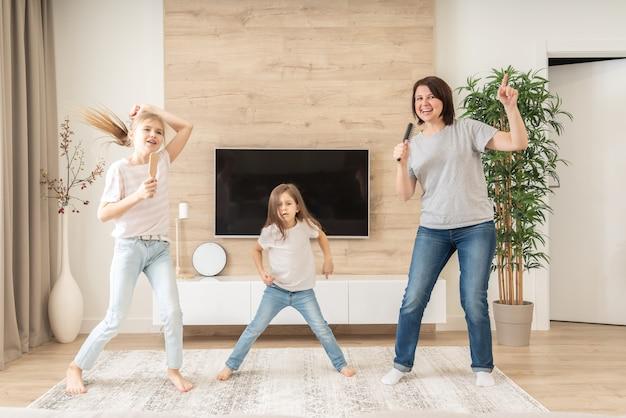 Счастливая мать и две дочери весело поют караоке в расчески. мать смеется, наслаждаясь забавным образом жизни с девочкой-подростком дома вместе.