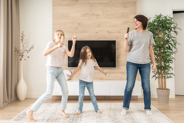 Счастливая мать и две дочери весело поют караоке в расчески.