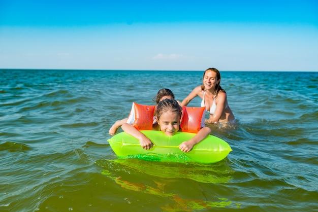 행복한 엄마와 두 명의 작은 긍정적 인 딸이 화창한 여름날에 에어 매트리스로 바다에서 목욕하고 수영합니다.