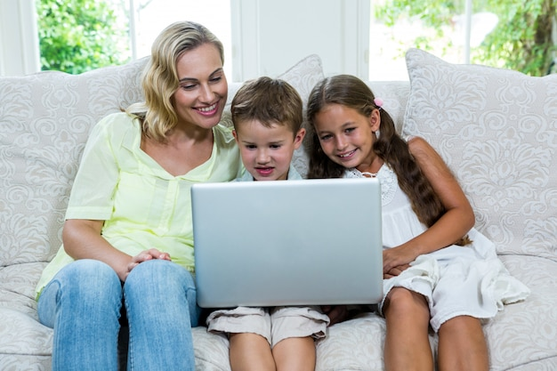 Happy mother by son and daughter using laptop at home