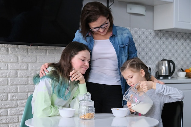 Happy mother caring for daughters in kitchen