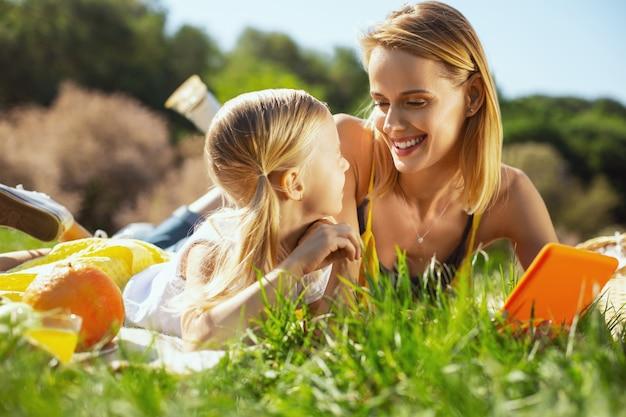 해피 어머니. 야외에서 딸과 함께 휴식을 취하는 동안 웃고 명랑 대담한 어머니