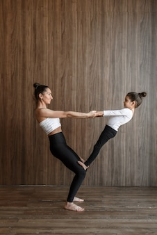 Happy mother and child little girl workout together yoga support in the gym