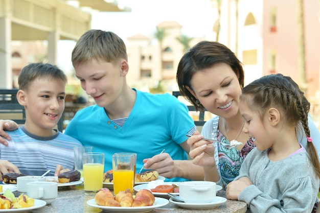 Happy mother and children  at breakfast on tropical resort