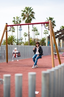 Happy mother and cute baby girl swinging on playground in summer park