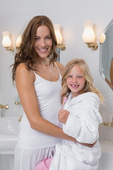 Happy mother and daughter in bathroom