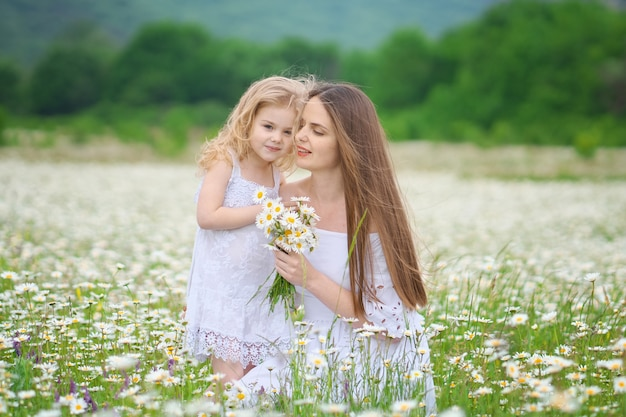 Happy mother and daughter in camomile meadow.