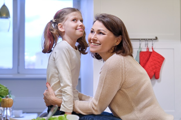 Happy mother and daughter child talking laughing in kitchen