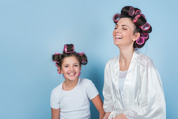 Happy mother and daughter in curlers smiling