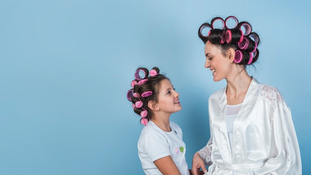 Happy mother and daughter in curlers