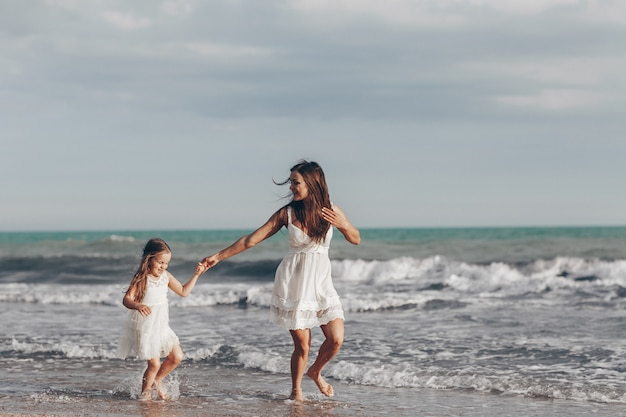 Happy mother and daughter enjoying sunny day on the beach