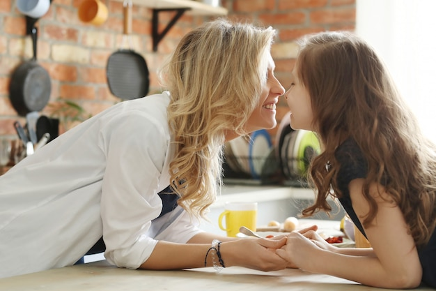 Happy mother and daughter having breakfast in the kitchen