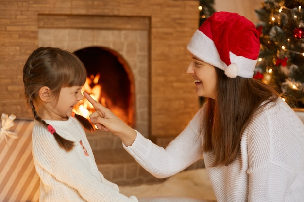 Happy mother and daughter having fun and joy of christmas time, sitting in living room against fir tree and fireplace