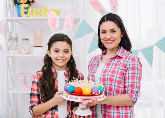 Happy mother and daughter holding colorful easter eggs nest on cakestand