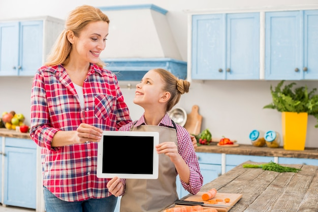 Happy mother and daughter holding digital tablet in hand looking at each other