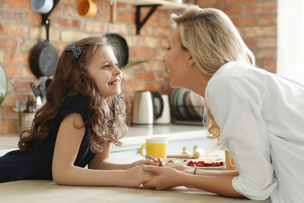Happy mother and daughter holding hands in kitchen