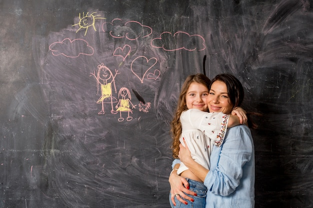 Happy mother and daughter hugging near chalkboard with drawing