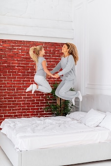 Happy mother and daughter jumping in bed